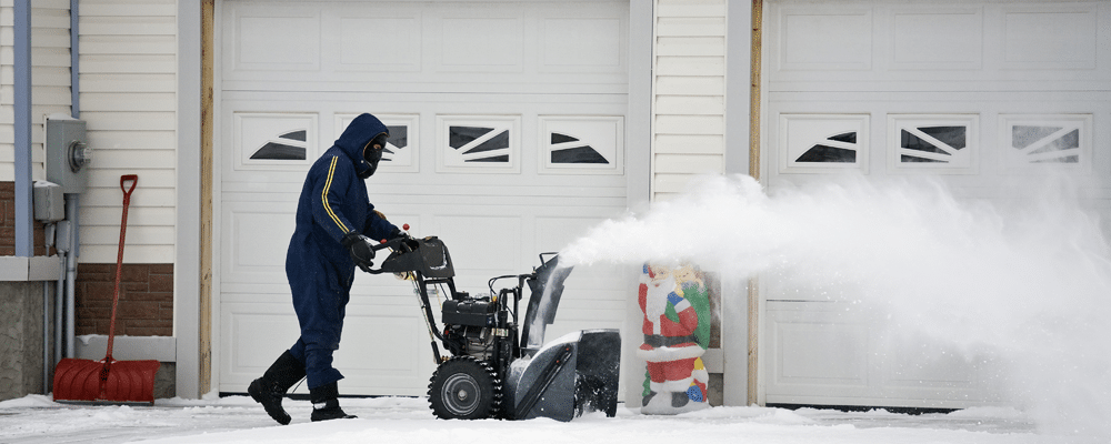 man removes snow in front of garage good for winterizing your home