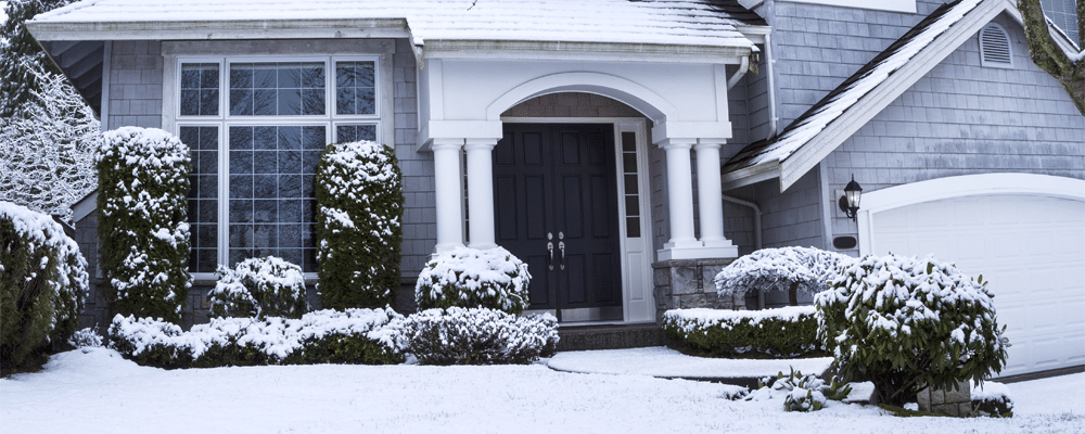 front view of a house with a garage and snow on the front yard